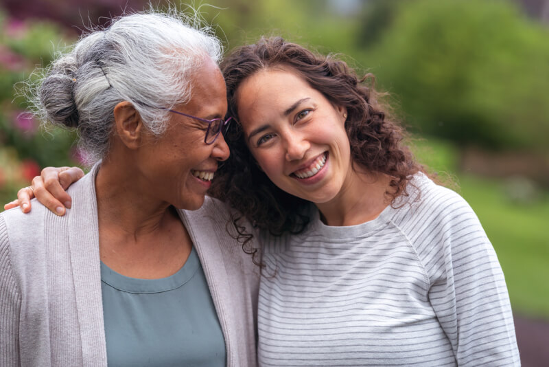 A senior woman embraces her millennial Eurasian daughter as they happily walk through a natural parkland area and enjoy their time together.