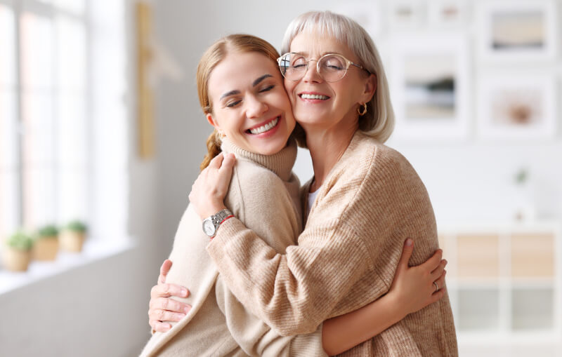 Delighted adult and senior women smiling with closed eyes and hugging each other