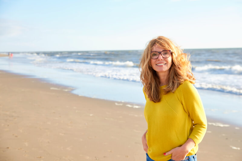 Portrait shot of beautiful smiling woman wearing sweater and jeans while relaxing on the beach