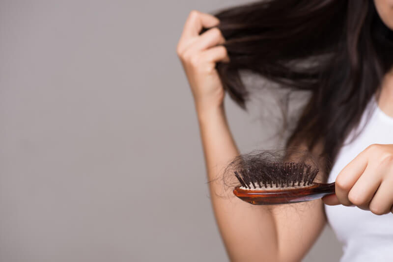 Woman show her brush with long loss hair and looking at her hair