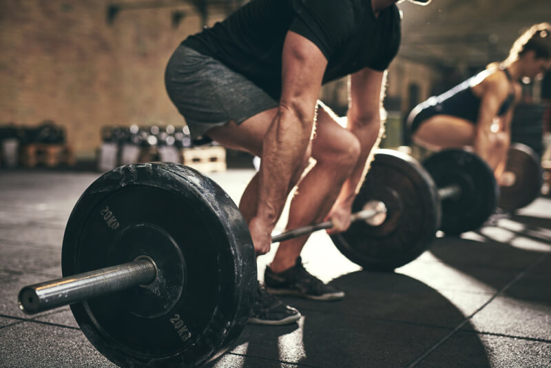 Fit people doing deadlift exercise in gym