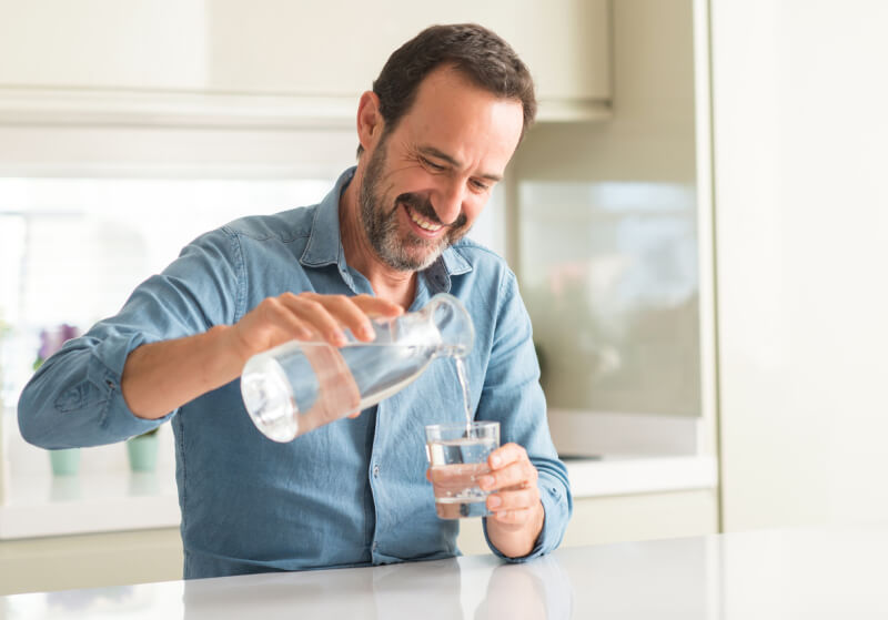Middle age man drinking a glass of water with a happy face