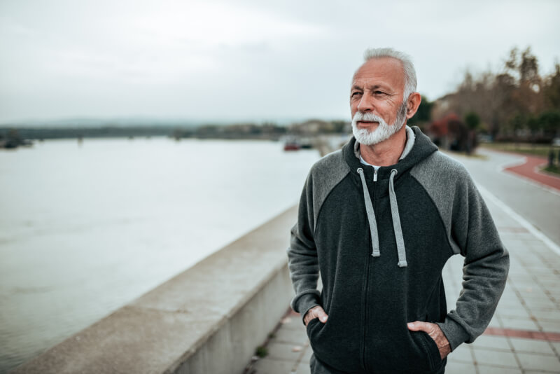 Portrait of a senior sportsman walking near the river in the city