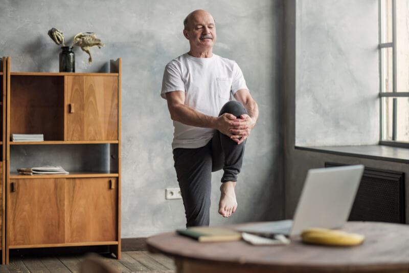 Senior handsome sportman doing stretching and balancing yoga exercise at home