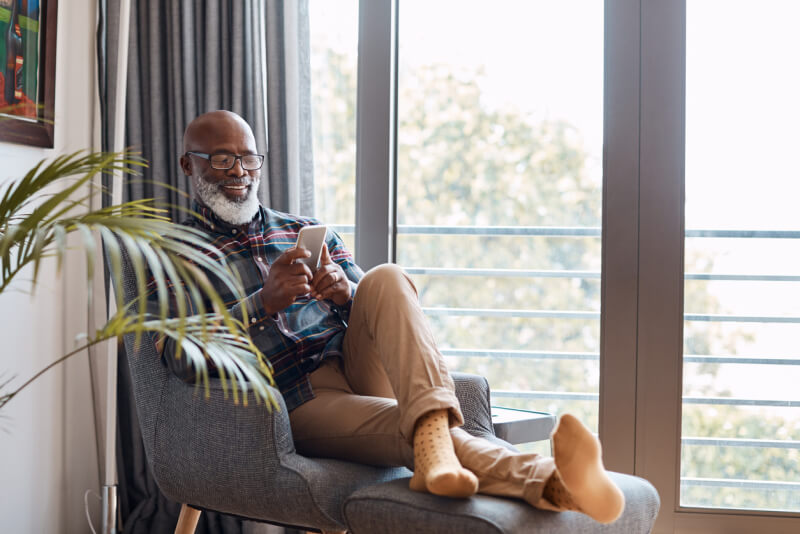 Shot of a mature man using a cellphone while relaxing on a sofa at home